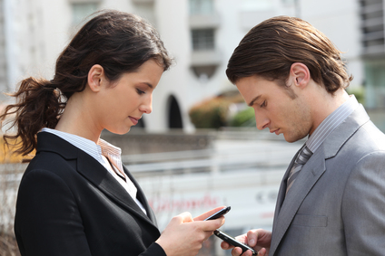 business couple texting on cellphones